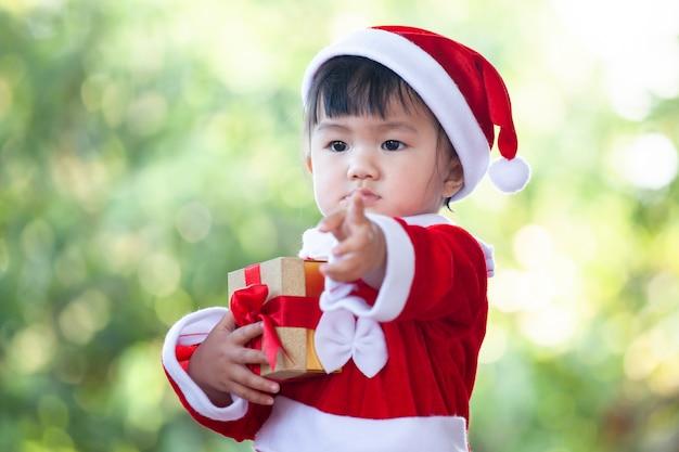 Leuk aziatisch babymeisje die santakostuum dragen die mooie giftdoos in hand houden