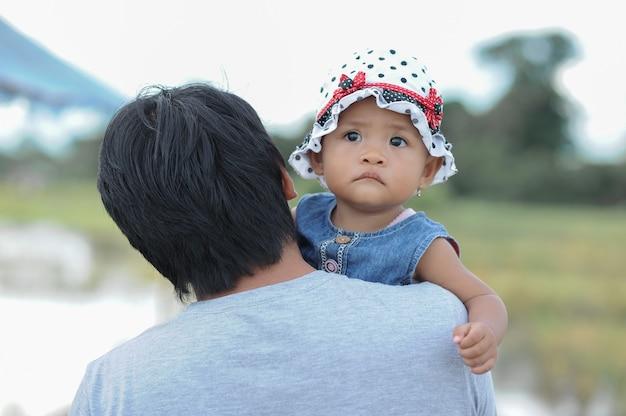 Leuk aziatisch babymeisje in de arm van zijn vader met hoed met stippen.
