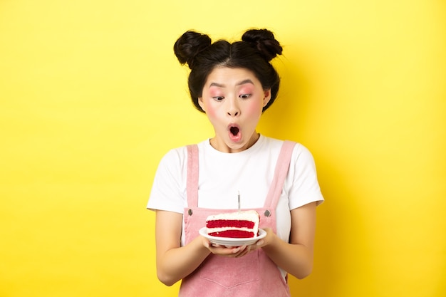 Leuk aziatisch feestvarken met lichte make-up, kaars blazen op de taart, wens maken, staande op geel