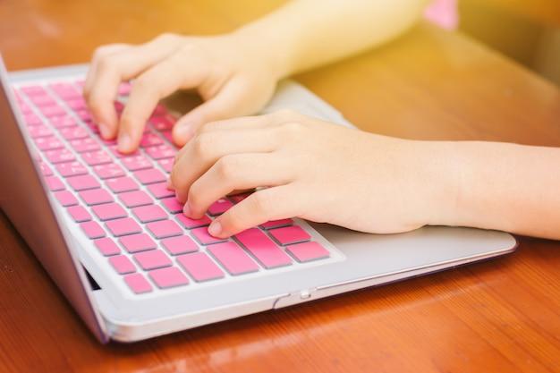 Leuk aziatisch jong meisje die thuiswerk met laptop thuis doen