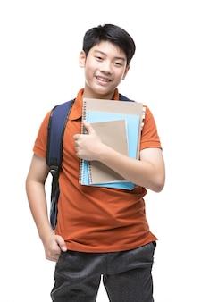 Leuk aziatisch kind met schoolkantoorbehoeften op wit.
