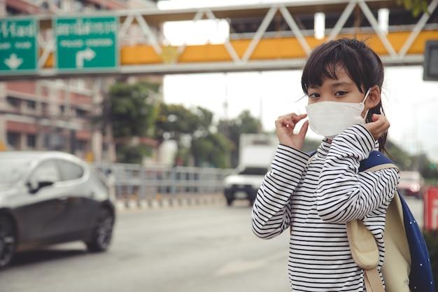 Leuk aziatisch kindmeisje dat een beschermingsmasker draagt tegen luchtsmogvervuiling met pm 2.5 in de stad Premium Foto