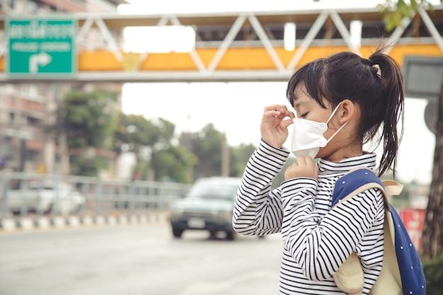 Leuk aziatisch kindmeisje dat een beschermingsmasker draagt tegen luchtsmogvervuiling met pm 2.5 in de stad