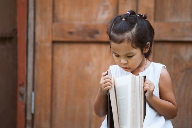 Leuk aziatisch kindmeisje dat een boek opent zij houdt van een boek te lezen
