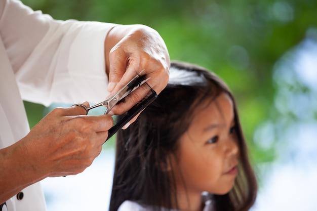 Leuk aziatisch kindmeisje dat kapsel door grootmoeder thuis krijgt