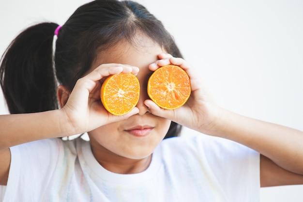 Leuk aziatisch kindmeisje dat verse sinaasappelen houdt die haar ogen behandelen