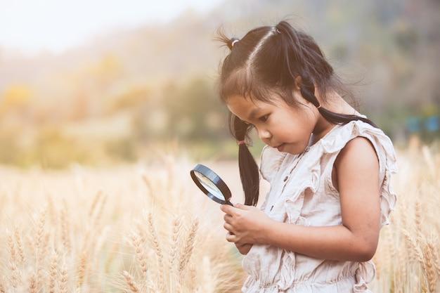 Leuk aziatisch kindmeisje die de oren van tarwe door een vergrootglas op het gerstgebied kijken