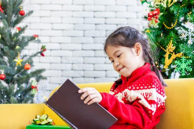 Leuk aziatisch kindmeisje die een boek in kerstmisviering lezen