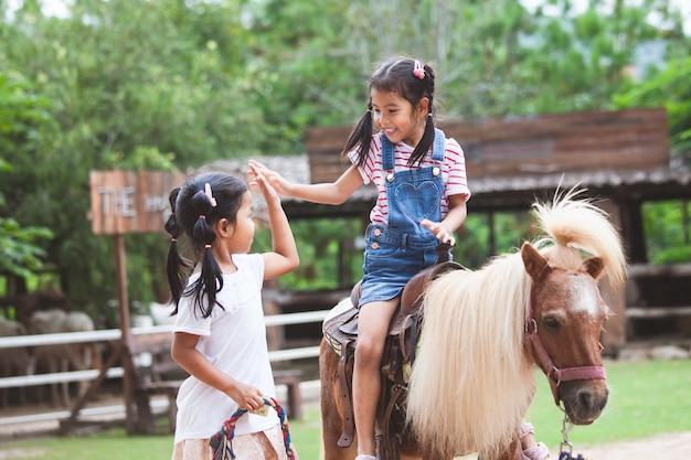 Leuk aziatisch kindmeisje die een poney berijden en hallo gebaar vijf met haar oudere zuster maken