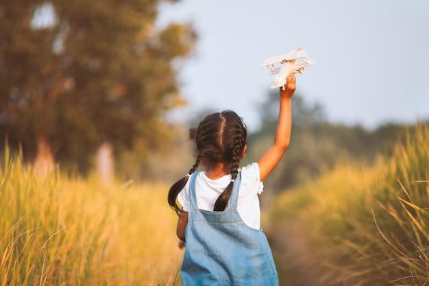 Leuk aziatisch kindmeisje die en met stuk speelgoed houten vliegtuig op het gebied lopen spelen