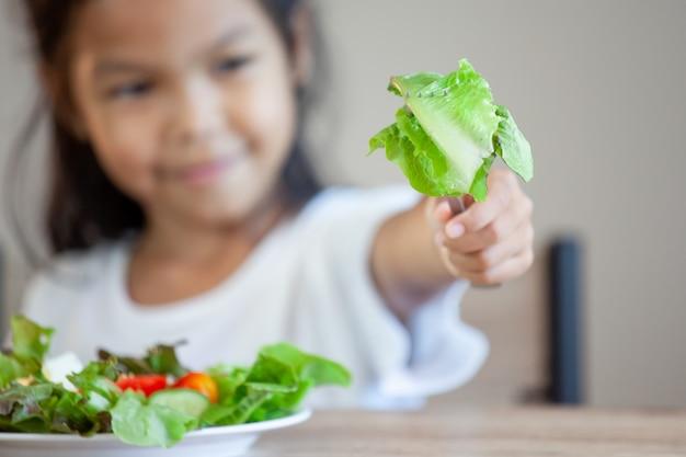 Leuk aziatisch kindmeisje die gezonde groenten en melk voor haar maaltijd eten
