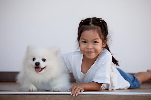 Leuk aziatisch kindmeisje die met haar spitz hond met pret en geluk spelen
