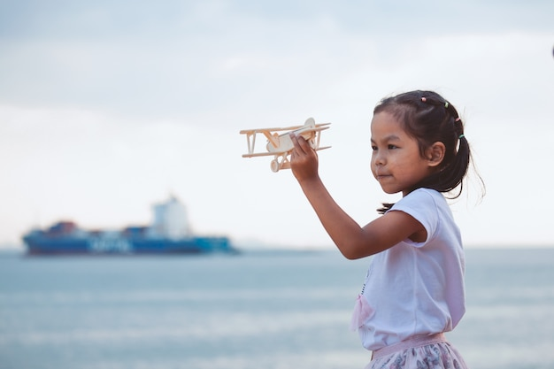 Leuk aziatisch kindmeisje die met stuk speelgoed houten vliegtuig in het strand met geluk spelen
