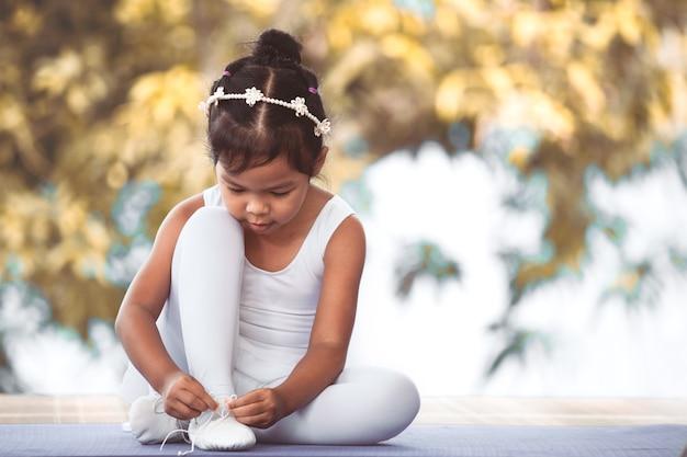 Leuk aziatisch kindmeisje die op voeten pointe schoenen binden die voor het praktizeren van een ballet voorbereidingen treffen