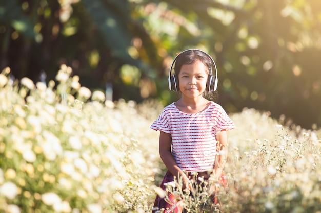 Leuk aziatisch kindmeisje die pret hebben om de muziek in hoofdtelefoons op bloemgebied te luisteren