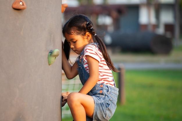 Leuk aziatisch kindmeisje die pret hebben te spelen en op de rotsmuur beklimmen in de speelplaats
