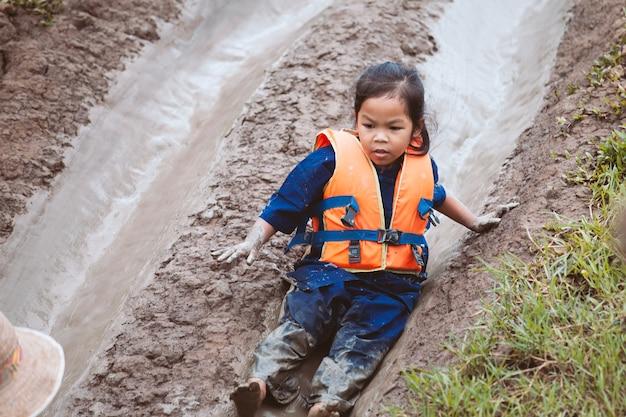 Leuk aziatisch kindmeisje die reddingsvest dragen die pret hebben om schuif met modderig te spelen