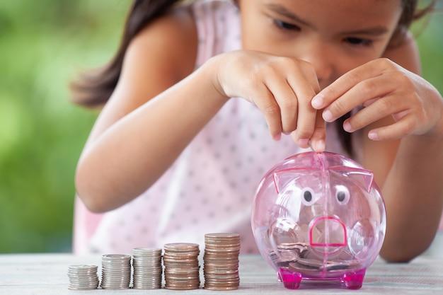 Leuk aziatisch kindmeisje die stapels muntstukken maken en geld zetten in spaarvarken