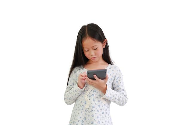 Leuk aziatisch klein kindmeisje die calculator over witte achtergrond gebruiken. onderwijs concept