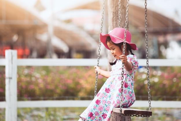 Leuk aziatisch klein kindmeisje die roze hoed dragen speelt schommeling in de tuin met pret