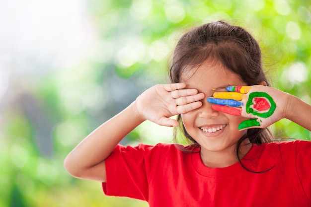 Leuk aziatisch klein kindmeisje met geschilderde handen die met pret en geluk glimlachen