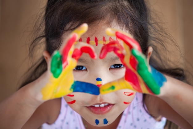 Leuk aziatisch klein kindmeisje met geschilderde handen maakt hartvorm kleurrijk met pret en liefde