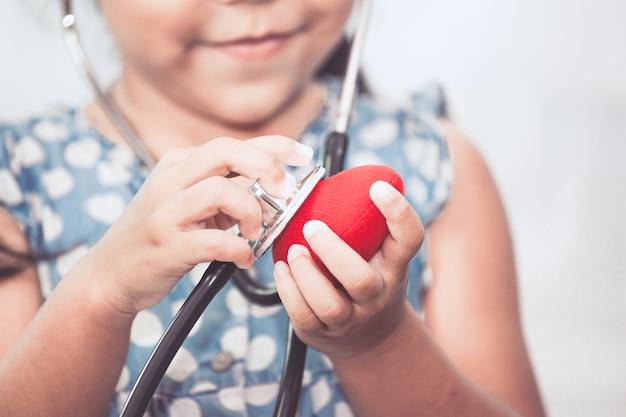 Leuk aziatisch klein kindmeisje met stethoscoop speelarts om rood hart ter beschikking te luisteren
