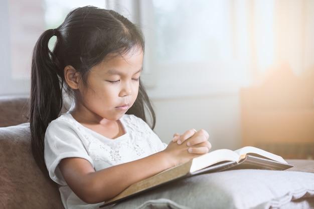 Leuk aziatisch klein kindmeisje sloot haar ogen en vouwde haar in gebed op een heilige bijbel