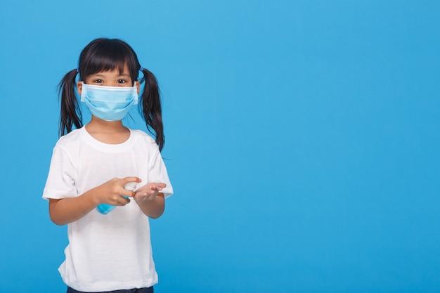 Leuk aziatisch meisje dat een masker draagt en haar handen met alcohol wast