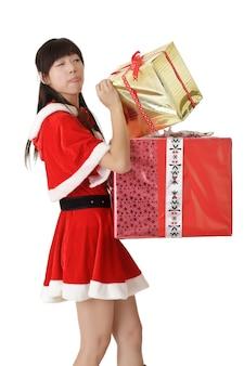 Leuk aziatisch meisje dat in santakleren de gift van kerstmis kijkt.