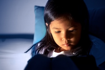 Leuk aziatisch meisje die digitale tablet gebruiken bij nacht in de slaapkamer in donkerblauwe kleurentoon