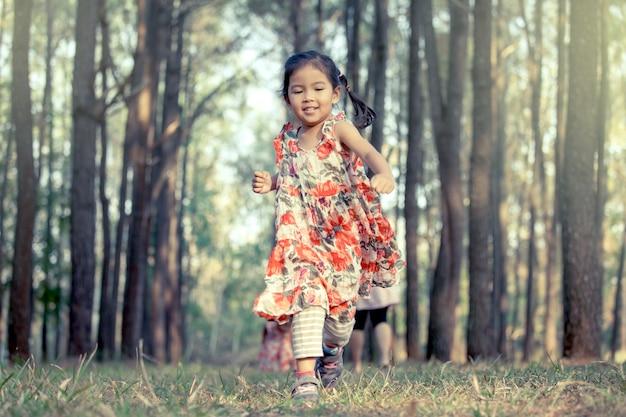 Leuk aziatisch meisje die in het park in uitstekende kleurentoon lopen