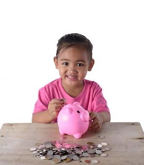 Leuk aziatisch meisje die muntstukken zetten die in spaarvarken op witte achtergrond worden geïsoleerd