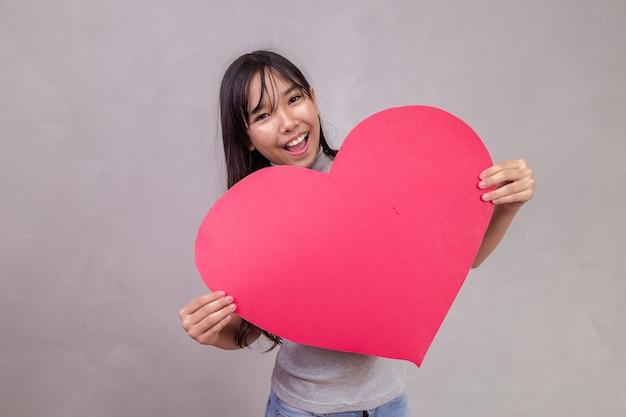 Leuk aziatisch meisje met een enorme hartkaart met ruimte voor tekst.