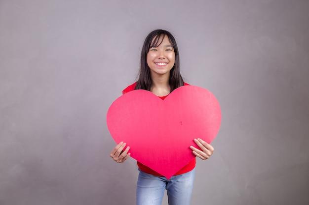 Leuk aziatisch meisje met een enorme hartkaart met ruimte voor tekst. Premium Foto