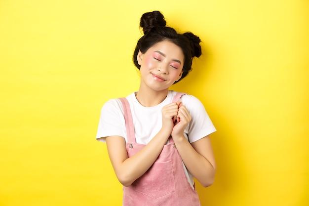 Leuk aziatisch meisje met make-up, ogen sluiten en onthouden mooi moment, hand in hand op hart dagdromen, staande op geel.