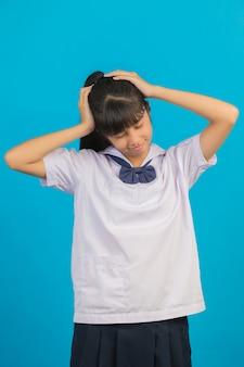 Leuk aziatisch schoolmeisje dat hoofdpijn op een blauw doet.