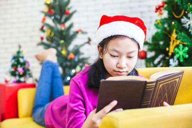 Leuk aziatisch tienermeisje die een boek in kerstmisviering lezen