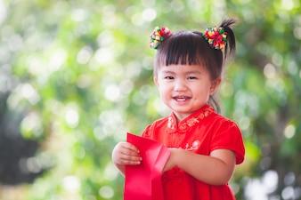 Leuk Aziatisch weinig kindmeisje dat en geld in rode envelop glimlacht krijgt