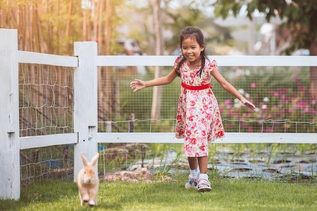 Leuk aziatisch weinig kindmeisje die een konijn met pret in de tuin lopen te vangen