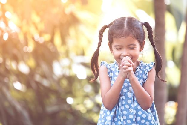 Leuk aziatisch weinig kindmeisje die met gevouwen haar hand voor geloof, spiritualiteit en godsdienstconcept bidden