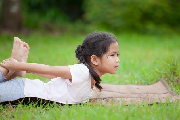 Leuk aziatisch weinig kindmeisje die oefening in het park doen