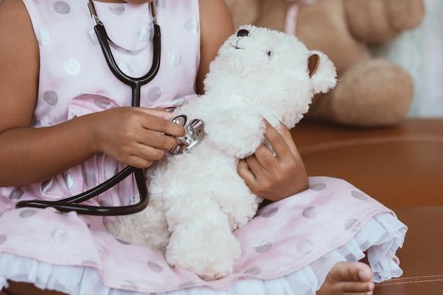Leuk aziatisch weinig kindmeisje met stethoscoop het spelen arts met teddybeer in uitstekende kleurentoon