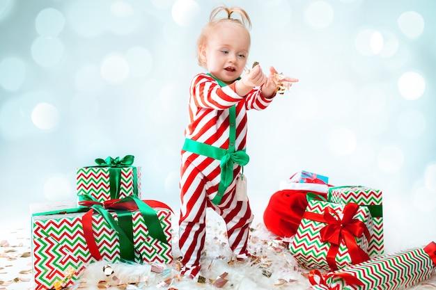 Leuk babymeisje 1 éénjarigen die santahoed dragen die tijdens kerstmis stellen
