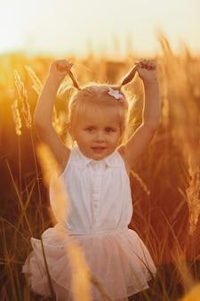 Leuk babymeisje 3-4 éénjarigen dichte omhooggaand. zomertijd. childhood. klein meisje met twee staarten. klein mooi meisje in het veld