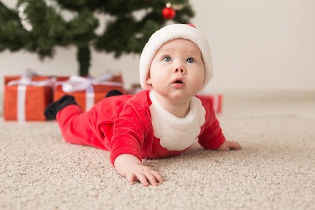 Leuk babymeisje die het kostuum van de kerstman dragen dat op vloer over kerstboom kruipt. vakantie seizoen.