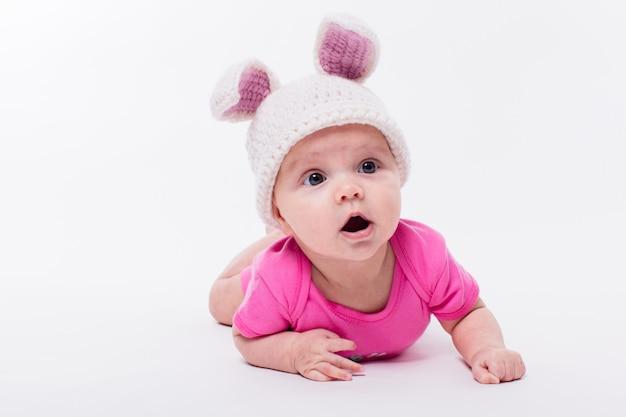 Leuk babymeisje die in een heldere roze t-shirt en een hoed met konijnoren liggen