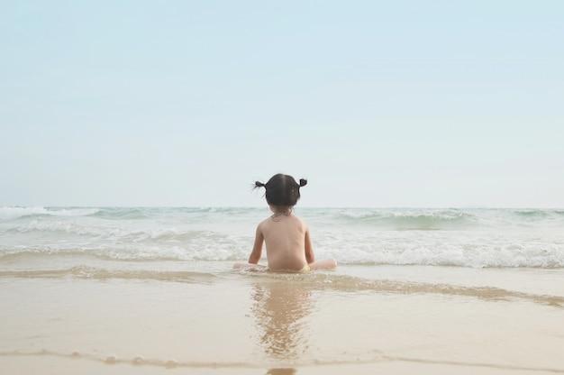 Leuk babymeisje kijkt uit naar de zee