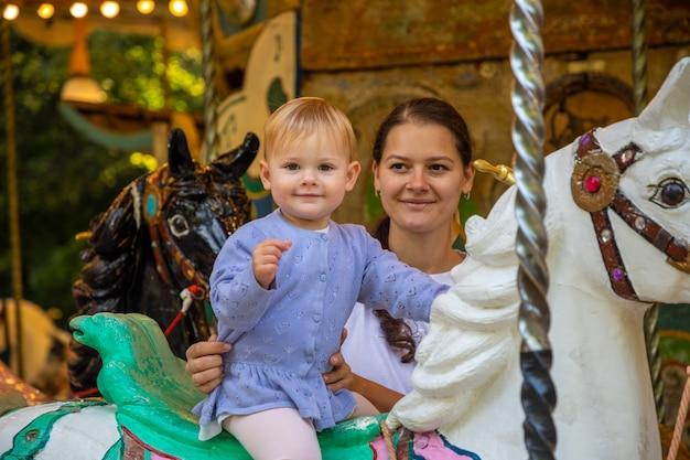 Leuk babymeisje met moeder op het paard van oude retro carrousel praag tsjechië