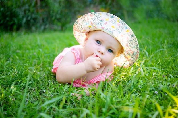 Leuk babymeisje op een groen gazon in de zomer in de zon die een hoed draagt